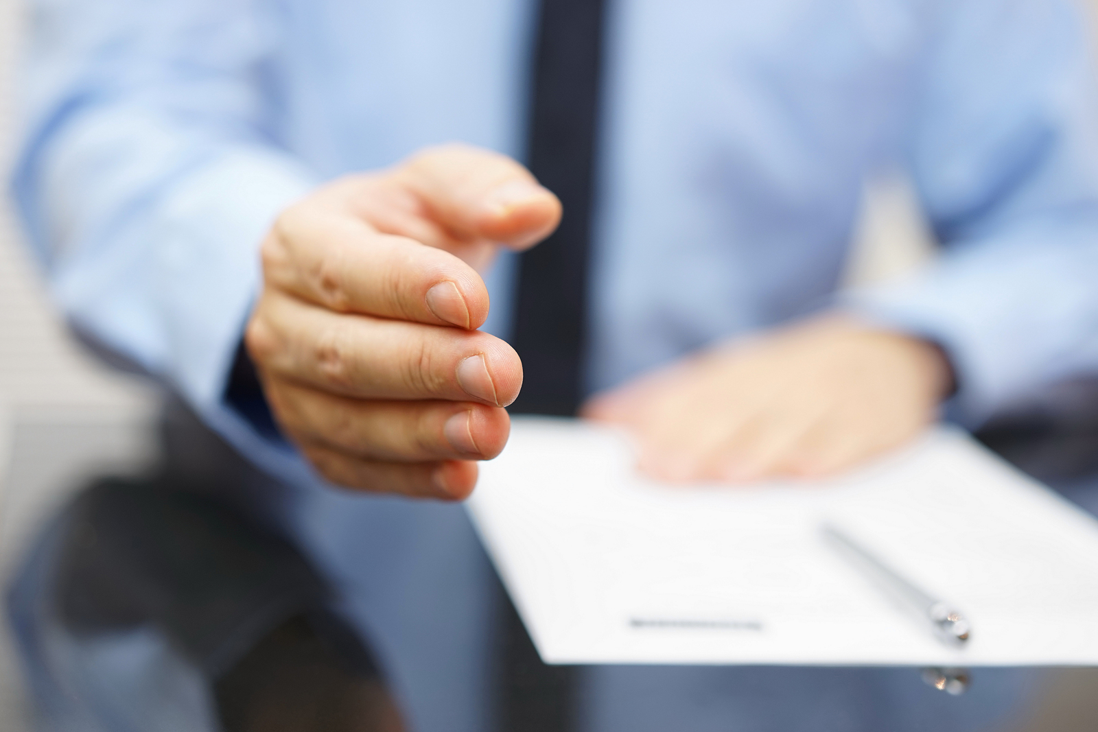 Businessman offering a handshake and contract to sing
